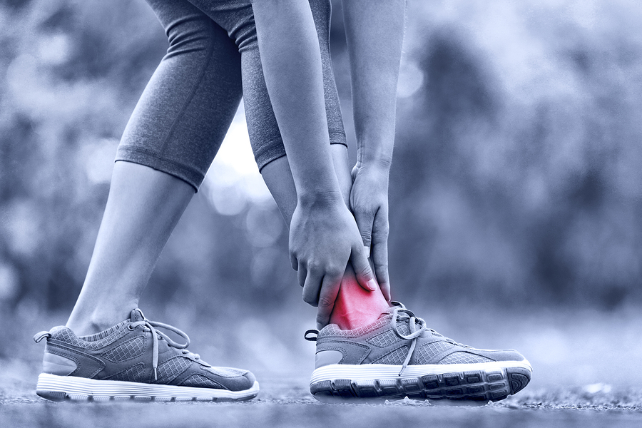 Broken twisted ankle - running sport injury. Female runner touch