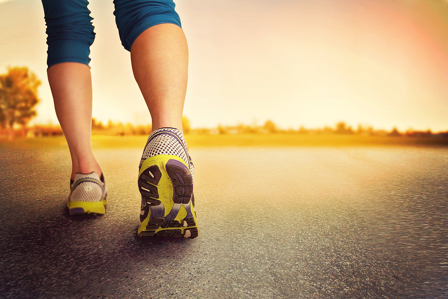 an athletic pair of legs on pavement during sunrise or sunset -