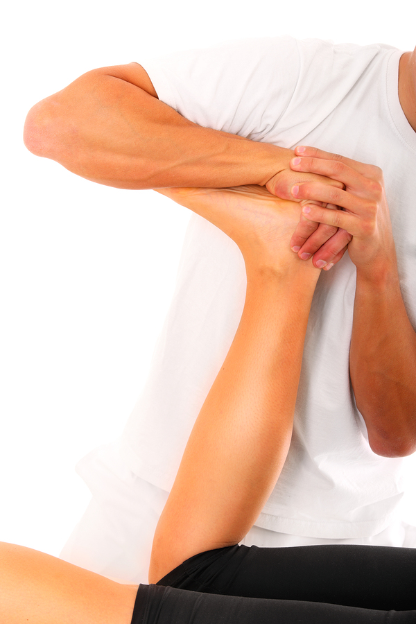 A picture of a physio therapist trying to fix the leg over white