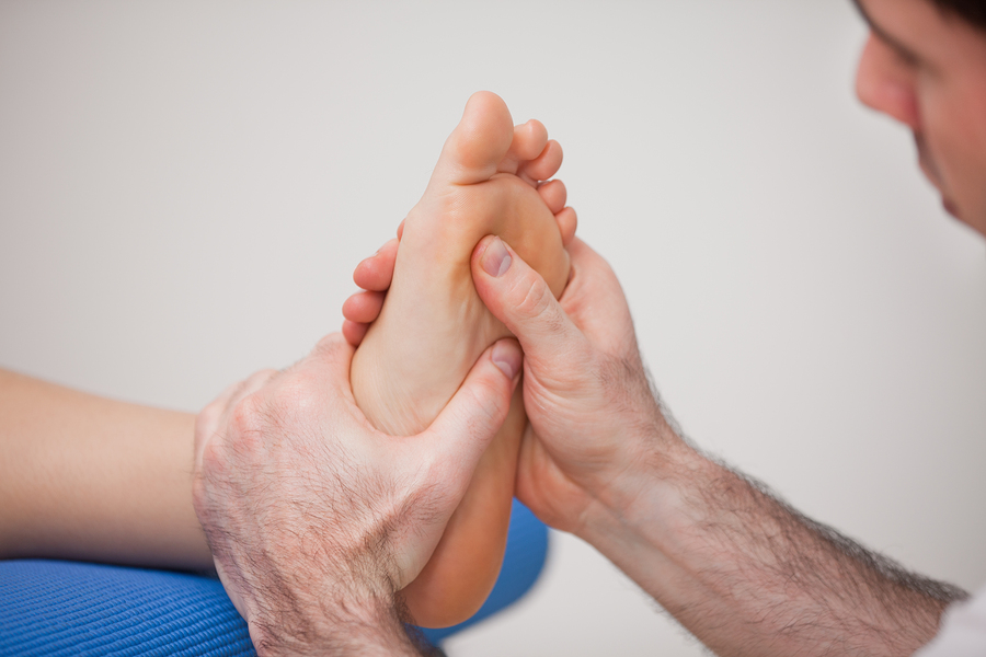 Podiatrist practicing reflexology on the foot of woman in a room